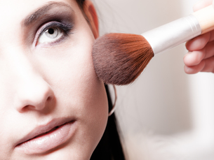 makeup artist applying powder rouge with brush on female checkの写真素材 [FYI00675989]