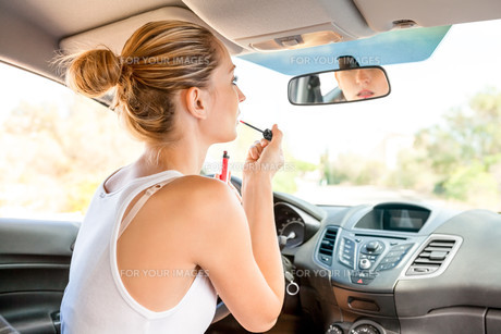 young woman putting on lipstick in the rearview mirror of your carの写真素材 [FYI00677085]