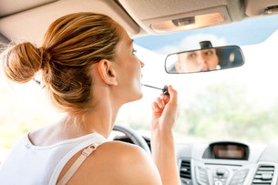young woman putting on lipstick in the rearview mirror of your carの写真素材 [FYI00677087]