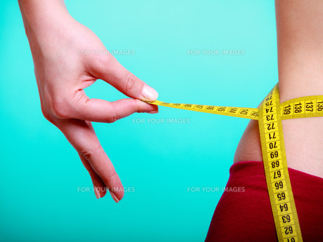diet. fitness woman fit girl with measure tape measuring her waistの写真素材 [FYI00677509]