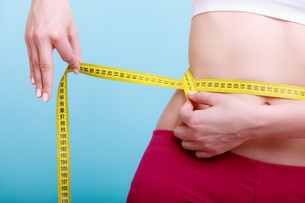 diet. fitness woman fit girl with measure tape measuring her waistの写真素材 [FYI00677510]