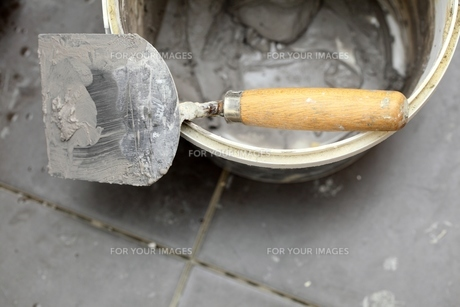 dirty trowel and bucket on building site. renovation at homeの素材 [FYI00677788]