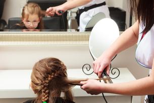hairdresser straightening hair little girl child in hairdressing beauty salonの写真素材 [FYI00678655]