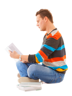 man college student sitting and reading book studying for examの写真素材 [FYI00678753]