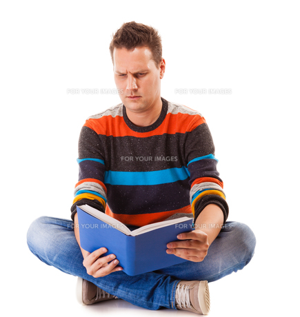 male student reading a book preparing for exam isolatedの写真素材 [FYI00679098]