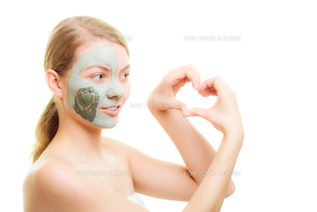 skin care. woman in clay mud mask on face with heart on the cheek isolated on white. girl showing symbol of love with hands. beauty treatment.の写真素材 [FYI00679154]