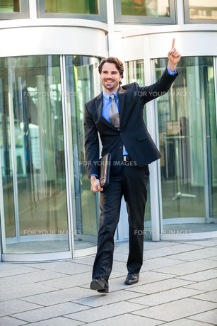 attractive young businessman jubilation in front of a business buildingの写真素材 [FYI00681400]