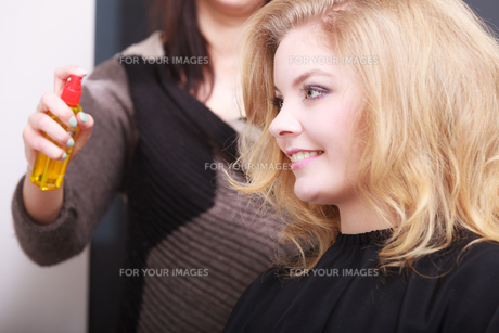 hairstylist with hairspray and female client blond girl in salonの素材 [FYI00681880]