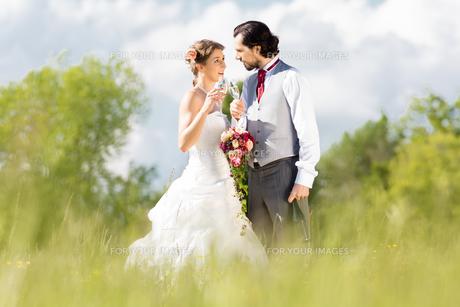 wedding couple celebrating with champagne outdoors weddingの写真素材 [FYI00682802]