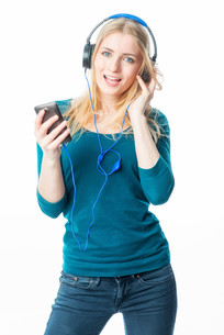 blond girl with headphones and smartphoneの写真素材 [FYI00683339]