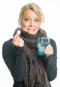 sick blond woman effervescent tablet dissolves in waterの写真素材 [FYI00683432]