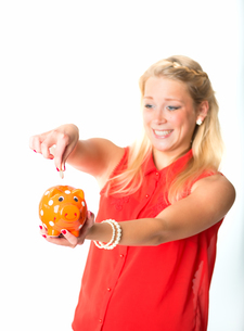 blonde woman with piggy bankの写真素材 [FYI00683530]