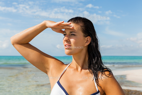 young attractive woman with dark hair on the beach looking into the distanceの写真素材 [FYI00683661]