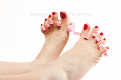 foot pedicure applying red toenails on whiteの素材 [FYI00684051]