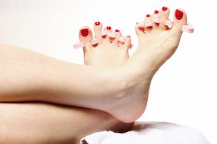 foot pedicure applying red toenails on whiteの素材 [FYI00684052]