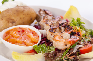 fried prawns on skewers with dipping sauce on mixed salad and baked potatoの写真素材 [FYI00685552]