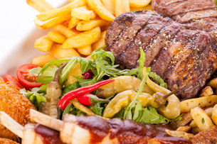 huge barbecue plate with mixed meat and steaks on lettuceの写真素材 [FYI00685556]