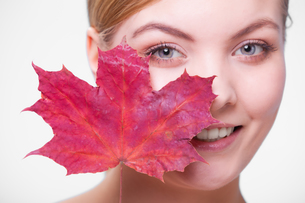skin care. portrait of young woman girl with red maple leaf.の写真素材 [FYI00686400]