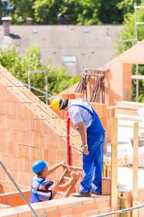 craftsmen control walls on building siteの写真素材 [FYI00686818]