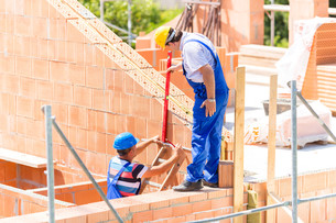 craftsmen control walls on building siteの写真素材 [FYI00686819]