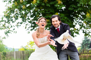 newlyweds with flying white dovesの写真素材 [FYI00686889]