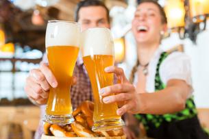 bavarian couple clinking beerの写真素材 [FYI00687839]