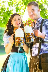 german couple in costume with beer and pretzelの写真素材 [FYI00687854]
