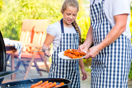 father and daughter grilling together on terraceの写真素材 [FYI00688517]