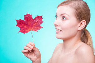 skin care. portrait of young woman girl with red maple leaf.の写真素材 [FYI00688730]