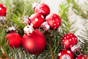 beautiful red christmas balls with small white dots with green fir branchesの写真素材 [FYI00688878]