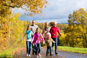 family in autumn walk in the woodsの写真素材 [FYI00691494]