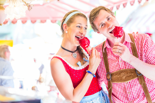 couple eating toffee apples at oktoberfestの写真素材 [FYI00691537]