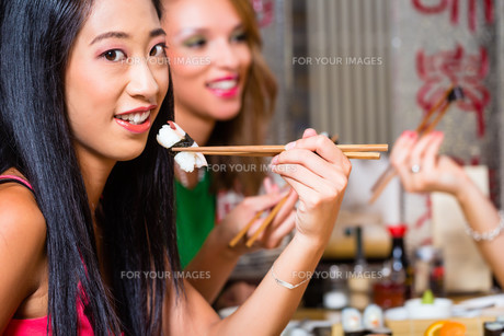 young people eat sushi in asia restaurantの写真素材 [FYI00691549]