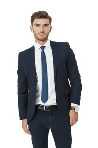 successful young businessman standing isolated in a relaxed pose with open jacketの素材 [FYI00693937]
