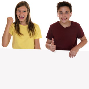 laughing children with empty poster and showing thumbs up copy spaceの写真素材 [FYI00695218]