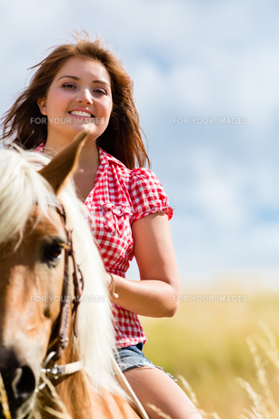 woman riding on horse in summer meadowの写真素材 [FYI00696150]