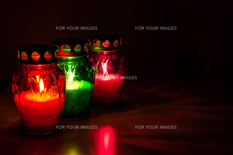 colored burning votive candles in the darkの写真素材 [FYI00697214]