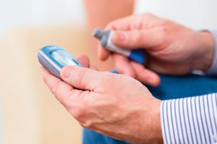 senior with diabetes use blood glucose meterの写真素材 [FYI00697826]