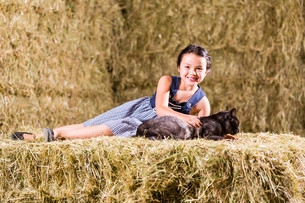 bavarian girl playing with cat on hayloftの写真素材 [FYI00697849]