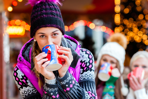 friends with mulled wine and christmas market on kandis?pfelの写真素材 [FYI00698178]