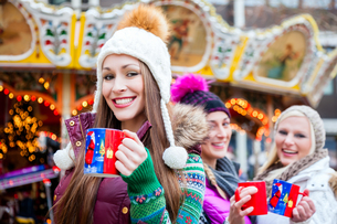 friends with mulled wine and christmas market on kandis?pfelの写真素材 [FYI00698179]