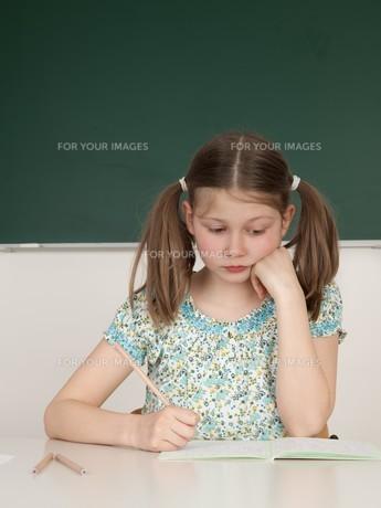 schoolgirl sitting at the table in schoolの写真素材 [FYI00699020]