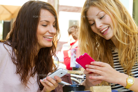 two girlfriends with mobile phone in cafeの写真素材 [FYI00699515]