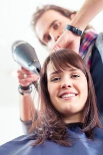 hairdresser f?hnt woman's hair in hair salonの写真素材 [FYI00700640]