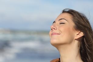 Closeup of a woman breathing fresh air on the beachの写真素材 [FYI00700675]