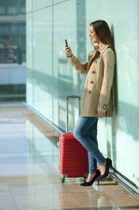 Traveler woman using a smart phone and waiting in an airportの写真素材 [FYI00700676]