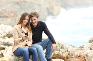 Couple sharing a smart phone on the beach on holidaysの写真素材 [FYI00701129]