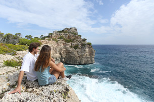 Couple sitting in a cliff watching ocean landscapeの写真素材 [FYI00701130]