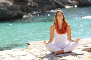 Relaxed girl doing yoga exercises on holidaysの写真素材 [FYI00701403]