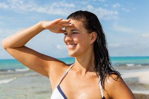 young attractive woman with dark hair on the beach looking into the distanceの写真素材 [FYI00701956]